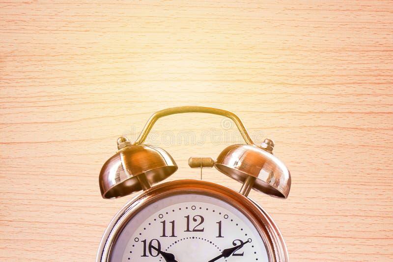 Fermez-vous vers le haut du rétro réveil sur une table en bois avec la brique brouillée photos stock