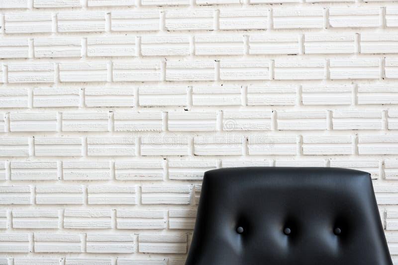 Fermez-vous vers le haut du sofa noir classique et du mur de briques blanc images libres de droits