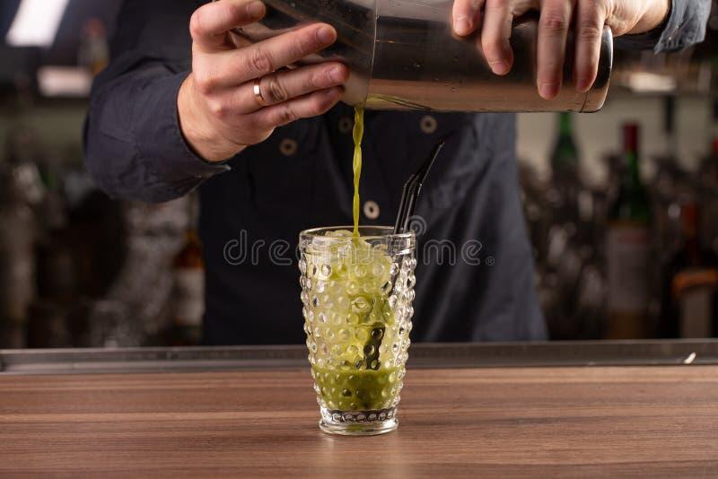 Fermez-vous vers le haut du tir du cocktail de versement de basilic de main de barman dans un verre de dispositif trembleur photos stock