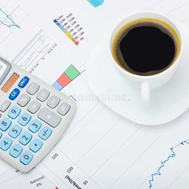 Fermez-vous vers le haut du tir d'une tasse et d'une calculatrice de café au-dessus de carte du monde et de diagrammes financiers image stock