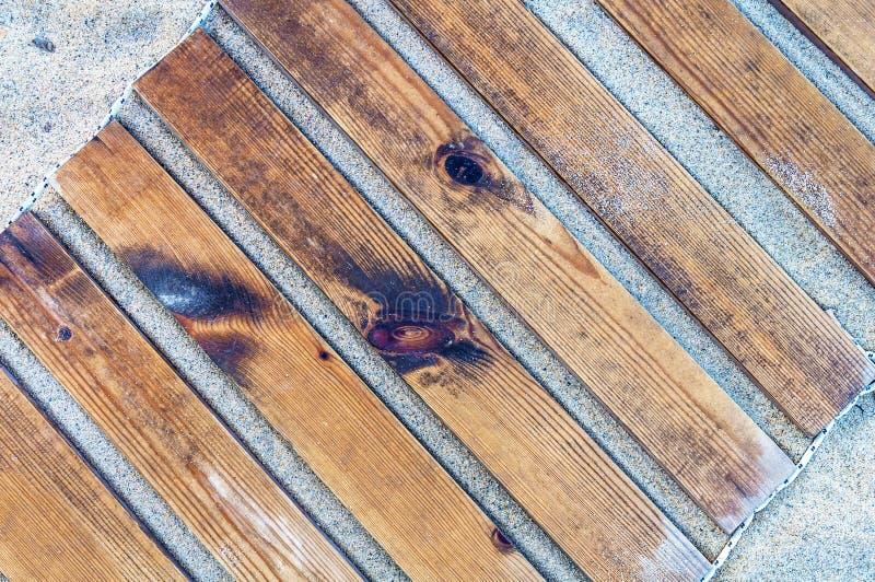 Fermez-vous vers le haut du tir d'une texture en bois de chemin de plage avec un certain sable image stock