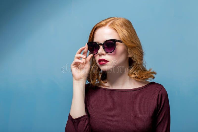 Fermez-vous vers le haut du tir de la jeune femme élégante dans des lunettes de soleil souriant sur le fond bleu Beau modèle feme image stock