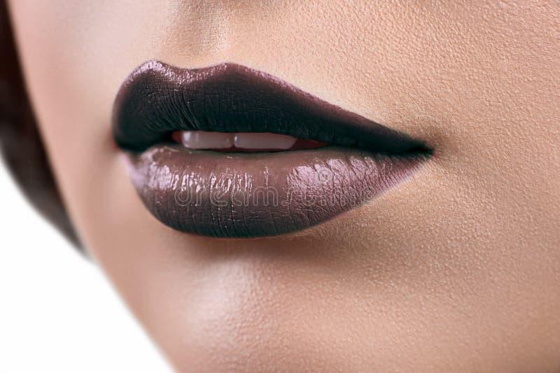 Fermez-vous vers le haut du tir des lèvres d'un glo de port de rouge à lèvres ou de lèvre de femme image stock
