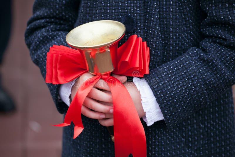 Fermez-vous vers le haut du tir des mains d'élève tenant la cloche d'école avec le ruban rouge De nouveau au concept d'école photos libres de droits