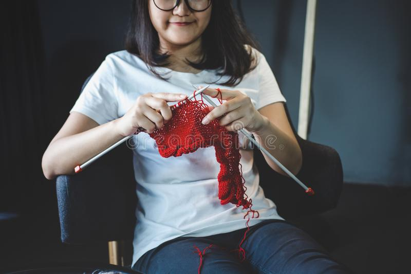 Fermez-vous vers le haut du tir des mains de jeune femme tricotant un handicra rouge d'écharpe photo libre de droits