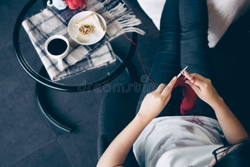 Fermez-vous vers le haut du tir des mains de jeune femme tricotant un handicra rouge d'écharpe photos stock