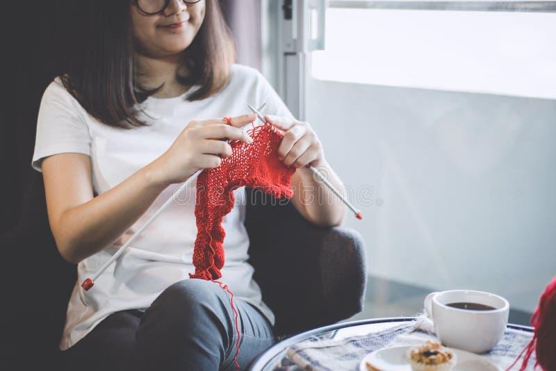 Fermez-vous vers le haut du tir des mains de jeune femme tricotant un handicra rouge d'écharpe photographie stock