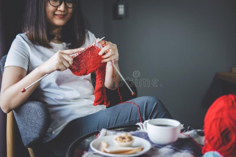 Fermez-vous vers le haut du tir des mains de jeune femme tricotant un handicra rouge d'écharpe photographie stock libre de droits