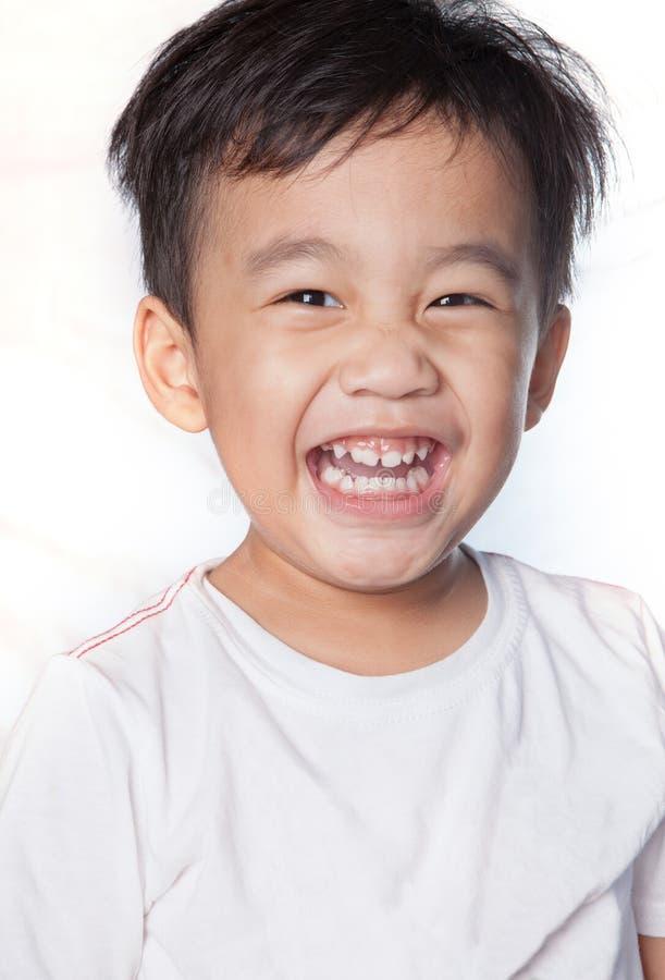 Fermez-vous vers le haut du tir principal du visage de sourire toothy d'enfants asiatiques photos stock