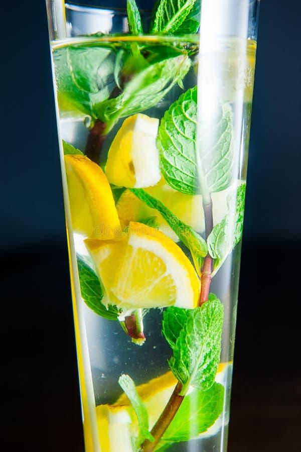 Fermez-vous vers le haut du verre de limonade avec des cales de menthe et de citron sur le fond foncé Foyer sélectif images stock