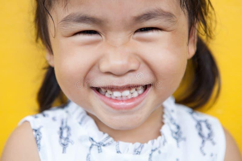 Fermez-vous vers le haut du visage du visage facial de sourire toothy d'enfant asiatique avec le happi images stock