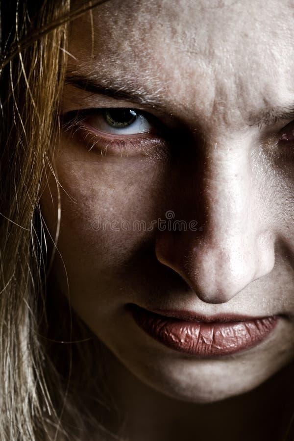 Fermez-vous vers le haut sur le visage effrayant bouleversé de mal fâché photographie stock