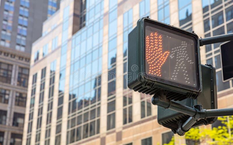 Fermi, non cammini il segnale stradale per i pedoni, fondo degli edifici per uffici della sfuocatura fotografie stock