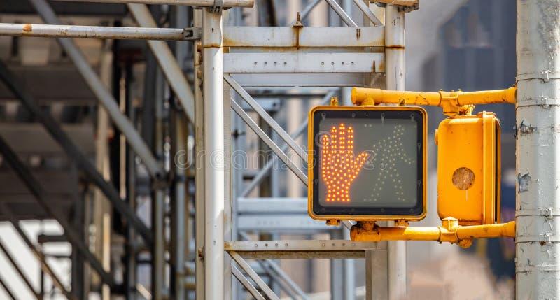 Fermi, non cammini il segnale stradale per i pedoni, fondo del cantiere della sfuocatura fotografia stock
