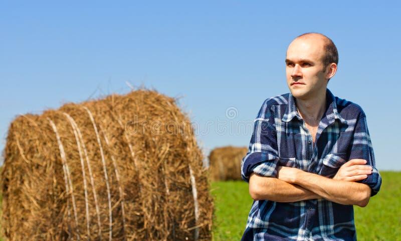 Fermier dans le domaine contre des balles de blé images stock