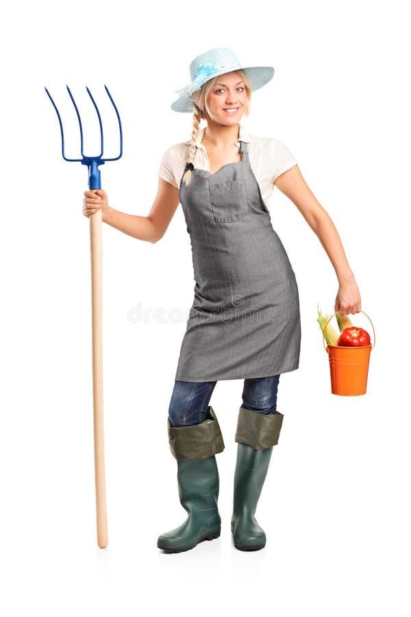 Fermier féminin retenant une fourche et une position photos libres de droits