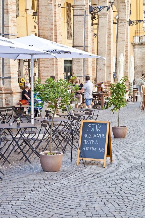 Fermo Italien - Juni 23, 2019: Folk som tycker om sommardag och mat på den utomhus- restaurangen och att vila royaltyfria bilder
