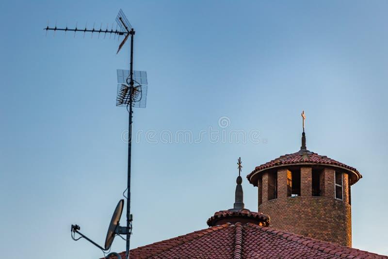 Fernsehantenne, -Satellitenschüssel und -katholische kreuzen stockbilder