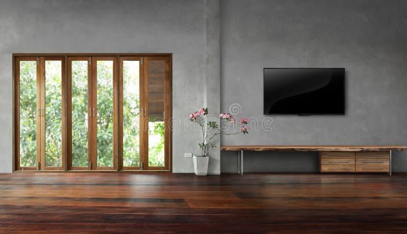 Fernsehen auf Betonmauer mit hohen Fenstern in den alten Bretterböden leeren Wohnzimmer stockfoto