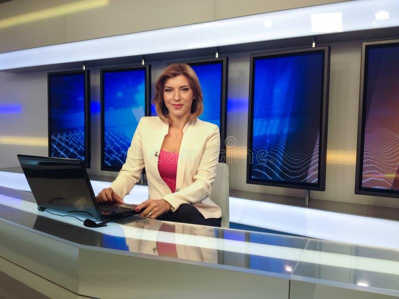 Fernsehreporter am Nachrichtenschreibtisch stockbilder