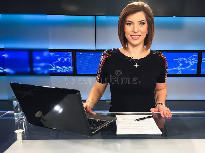 Fernsehreporter am Nachrichtenschreibtisch stockfotografie