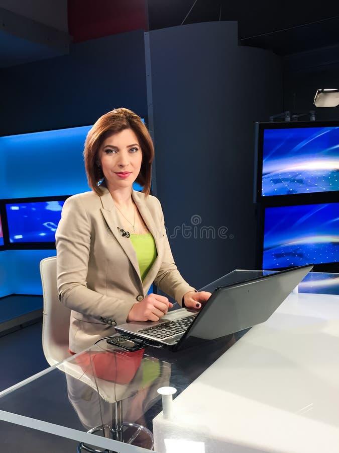 Fernsehreporter am Nachrichtenschreibtisch lizenzfreie stockbilder