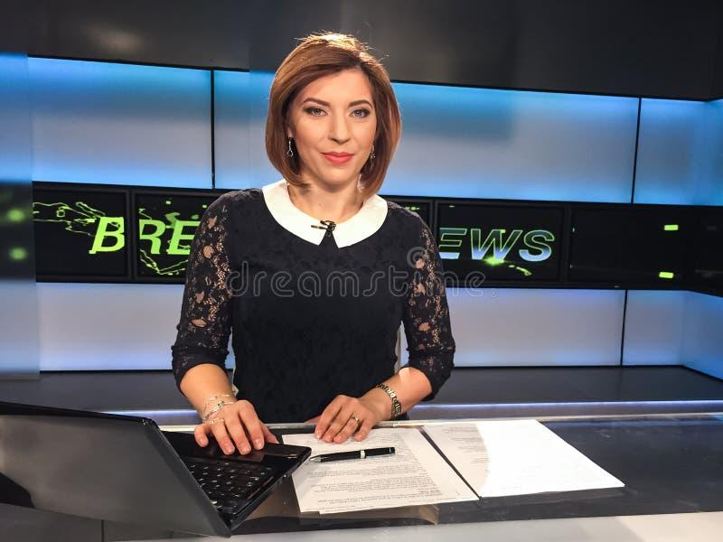Fernsehreporter am Nachrichtenschreibtisch stockbild