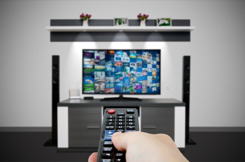 Fernsehsendungs-Multimediazusammensetzung im Raum und in der Fernbedienung in der Hand stockbild