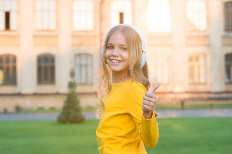 Fernunterricht Glückliches kleines Mädchen mit Kopfhörern Stereo-Sound Gute Geschichten hören Selbstbildung Kopfhörer stockfotografie
