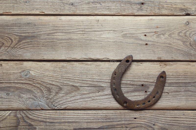 Ferradura oxidada na placa de madeira velha imagem de stock