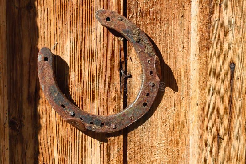 Ferradura oxidada no fundo de madeira velho Fora imagem em um dia ensolarado fotografia de stock
