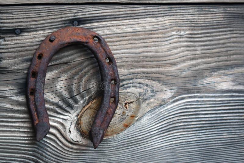 Ferradura oxidada velha em um fundo de madeira fotos de stock
