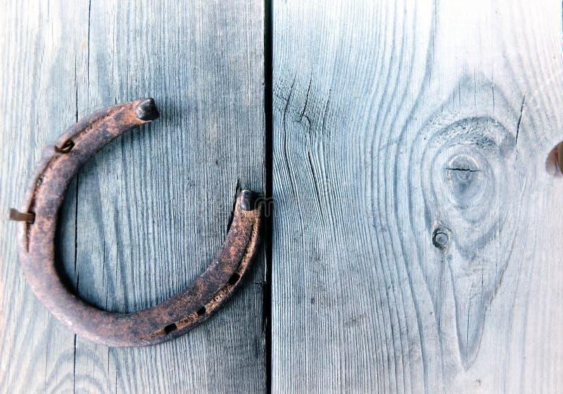 Ferradura oxidada velha na placa de madeira do vintage imagens de stock