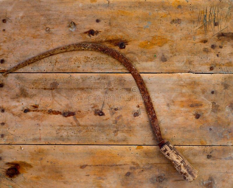 A ferramenta antiga da foice oxidou na madeira envelhecida do vintage fotos de stock royalty free