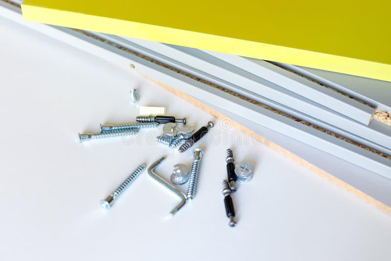 Ferramenta da asseguração, parafusos de conexão e chave de Allen para a mobília de montagem perto das fachadas e das paredes da g imagens de stock
