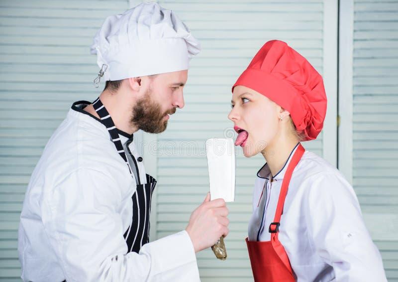 Ferramenta da faca do talhador da posse do cozinheiro chefe quando a mulher lamber a lâmina Cozinhar é 'sexy' Ferramenta do profi imagem de stock royalty free