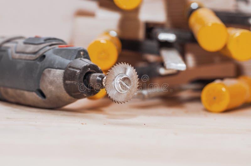 A ferramenta de Dremel com uma circular pequena instalada viu em uma boa de madeira fotos de stock