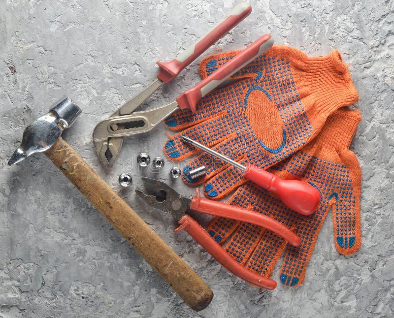 Ferramenta de funcionamento em uma superfície concreta cinzenta Trabalhe luvas, martelo, pinças, chave de fenda, alicates, chave  fotos de stock