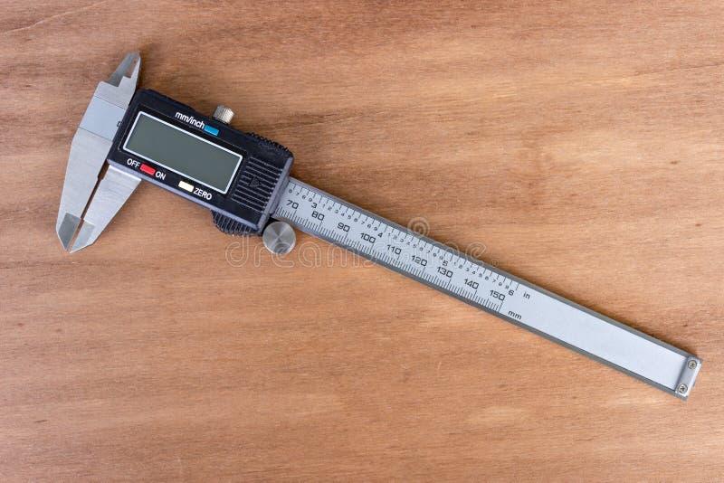 Ferramenta do compasso de calibre em um fundo de madeira fotografia de stock royalty free