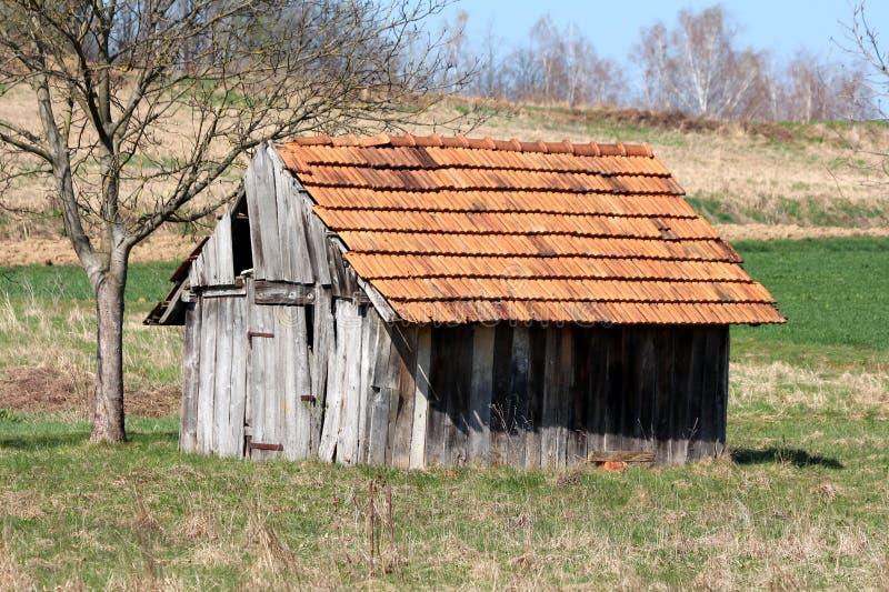 A ferramenta exterior dilapidada de madeira do vintage retro pequeno derramou com placas rachadas e as telhas de telhado quebrada imagem de stock royalty free