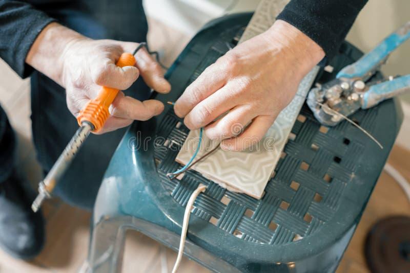 Ferramenta guardando masculina que repara, conexão do ferro de solda do fio elétrico, soldando com um ferro de solda imagem de stock royalty free