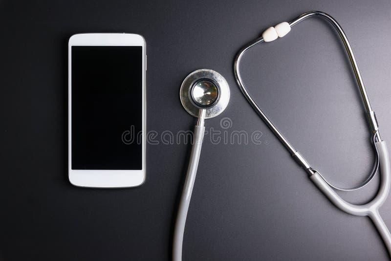 Ferramenta médica do estetoscópio sobre a superfície de um phon esperto móvel fotos de stock