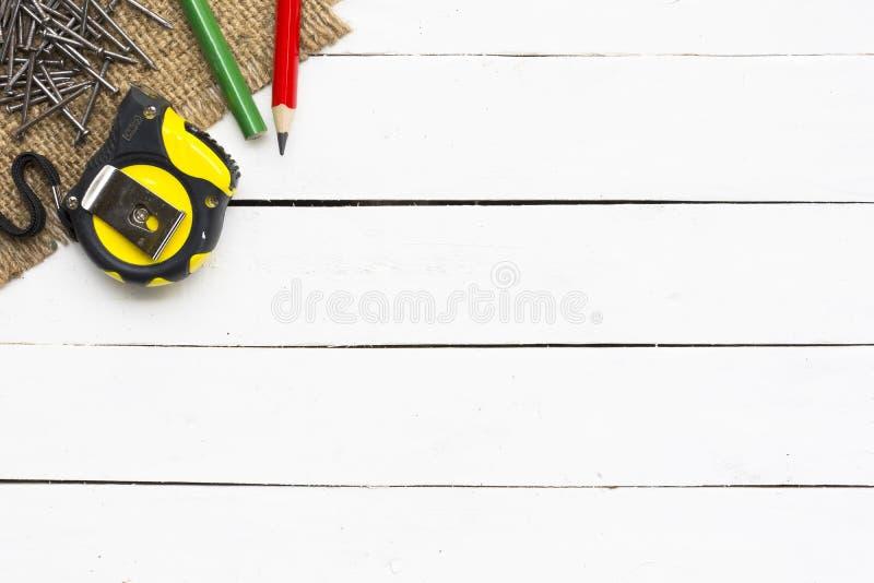 Ferramentas da carpintaria tais como a fita métrica com lápis e os pregos de madeira no fundo branco de madeira equipamento para  foto de stock royalty free