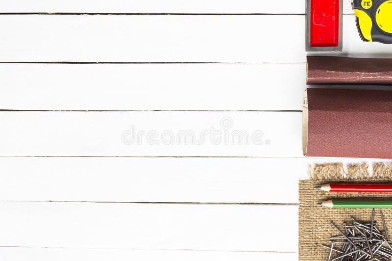 Ferramentas da carpintaria tais como a fita métrica com lápis e os pregos de madeira no fundo branco de madeira equipamento para  imagem de stock