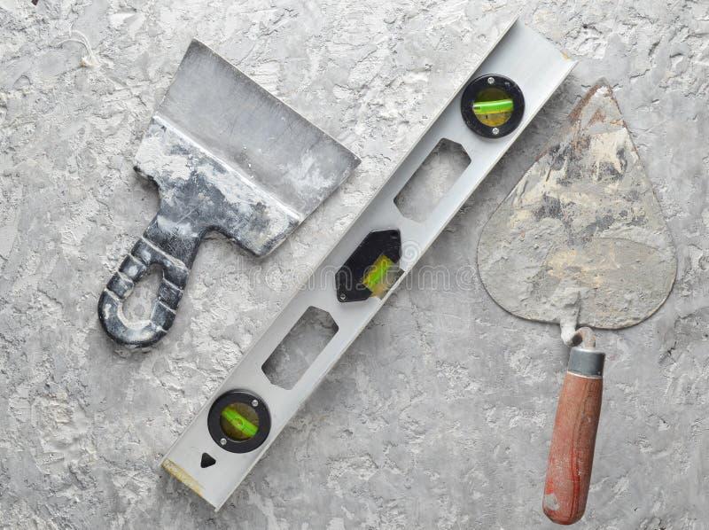 Ferramentas de construção em um fundo concreto cinzento Espátula, pá de pedreiro, nível, nível, vista superior foto de stock