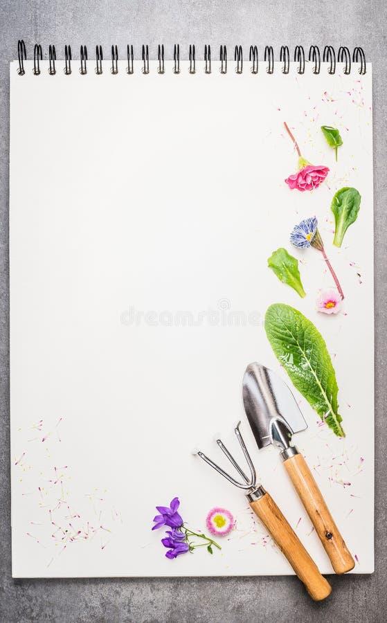 Ferramentas de jardim com flores e pétala no caderno vazio fotos de stock royalty free