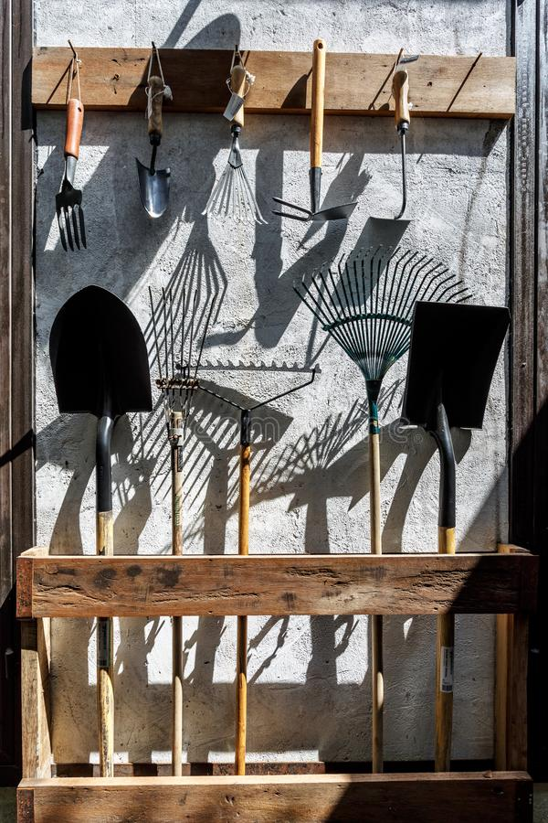 Ferramentas de jardim do metal da exploração agrícola como as pás e os ancinhos que penduram na parede fotografia de stock royalty free