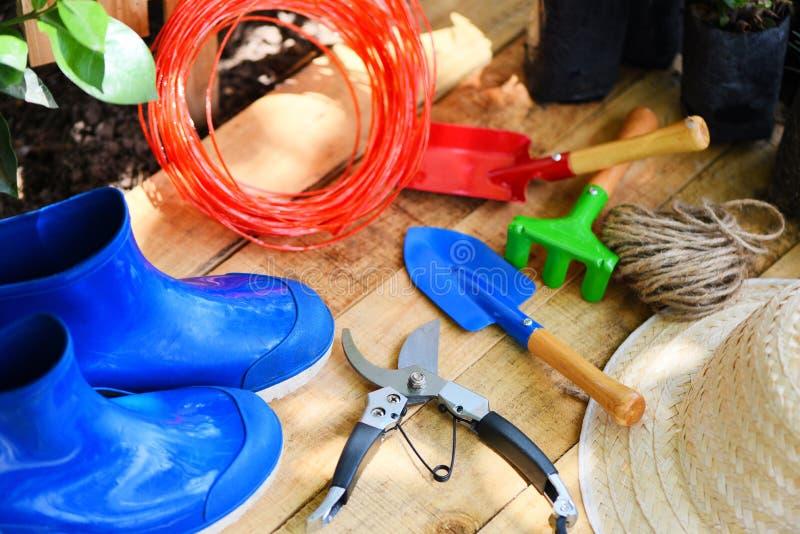 Ferramentas de jardinagem na placa de madeira com equipamento da pá de pedreiro de jardim da bota de borracha da corda das tesour fotografia de stock