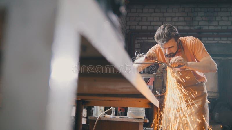 Ferramentas de moedura do metal com sparkles - forje a oficina imagem de stock