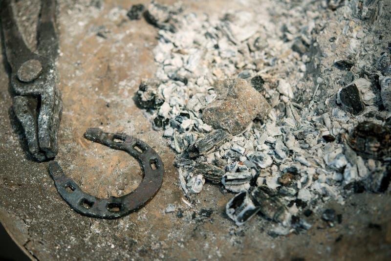 Ferramentas de um ferreiro no fórceps das cinzas e em uma ferradura imagens de stock